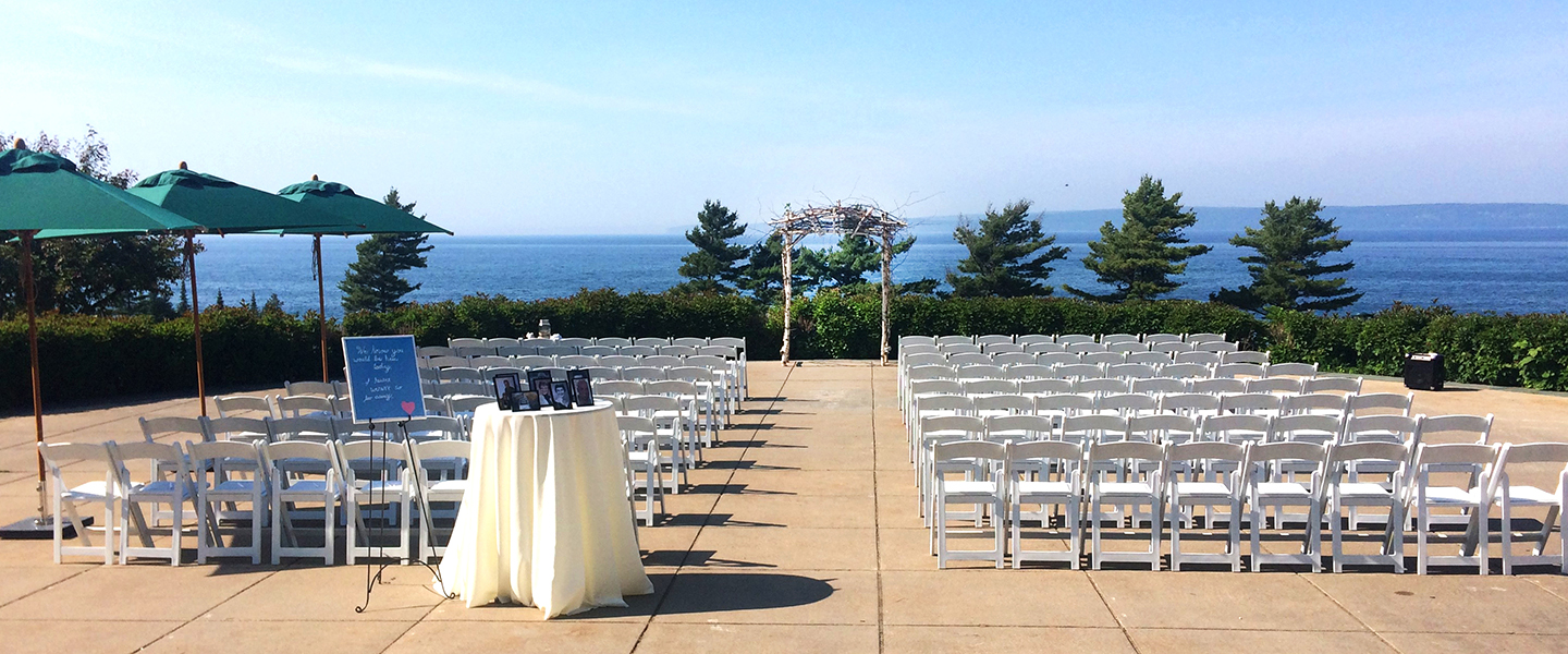 Outdoor wedding ceremony setup with rustic arch on Bay Harbor Golf Club's large paved event space overlooking Lake Michigan